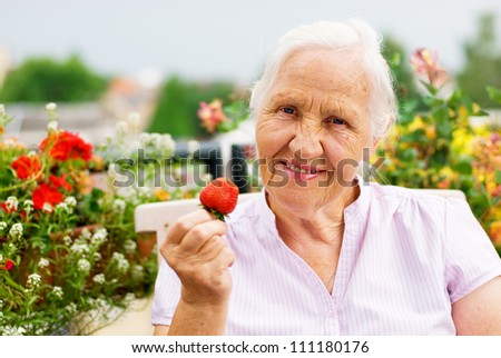 Elderly smiling woman sitting on the terrace, holding a strawberry - stock photo
