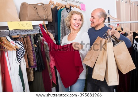 Elderly spouses 50s buying new dress and smiling in boutique