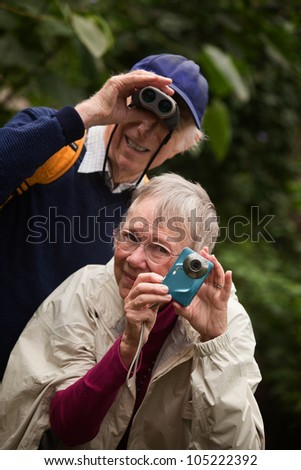 Elderly tourists with camera and binoculars in the woods - stock photo
