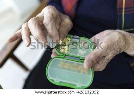 Elderly Turkish woman taking pills from green colored medicine box closeup view - stock photo