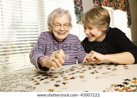 Elderly woman and a younger woman work on a jigsaw puzzle.  Horizontal shot. - stock photo