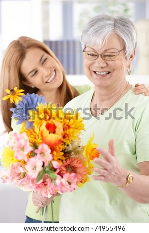 Elderly woman and daughter smiling happily at mother's day, having flowers.? - stock photo