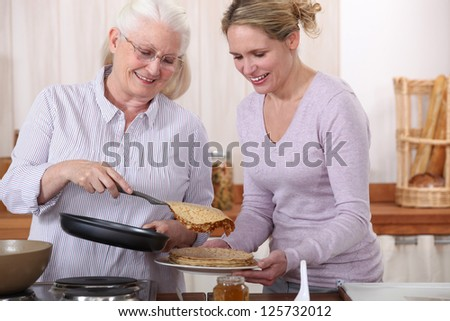 Elderly woman and daughter with pancakes - stock photo