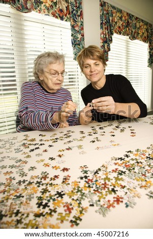 Elderly woman and younger woman work on a jigsaw puzzle together.  Vertical shot. - stock photo