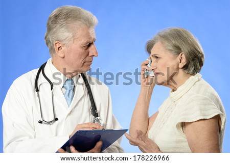 Elderly woman came to the doctor over a blue background
