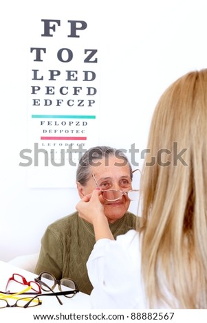 Elderly woman choosing a pair of glasses at the optician - stock photo