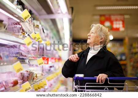 Elderly woman choosing dairy produce in supermarket, shopping for dairy produce  in department of a grocery store/supermarket ( color toned image ) - stock photo