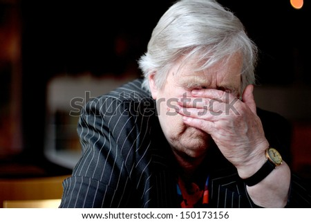 Elderly woman cover her face with hand - stock photo
