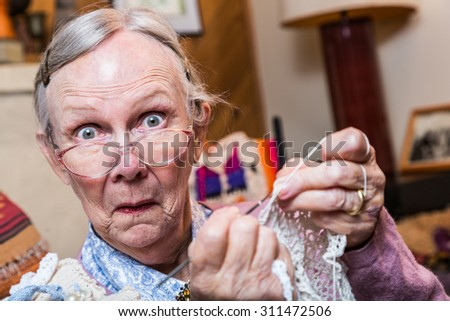 Elderly woman crocheting while looking at camera - stock photo