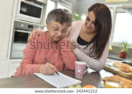 Elderly woman doing crossword while homecare helps at home - stock photo