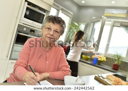 Elderly woman doing crosswords while homecare helps at home - stock photo