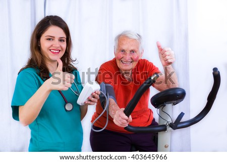 Elderly woman doing sport effort on a spinning bike having hear hart rate and blood pressure monitored.