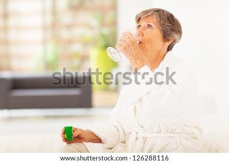 elderly woman drinking medicine at home - stock photo