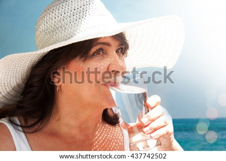 Elderly woman drinking water by the sea