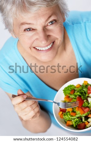 Elderly woman eating salad - stock photo