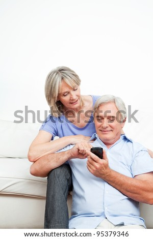 Elderly woman explaining senior man smartphone at home - stock photo