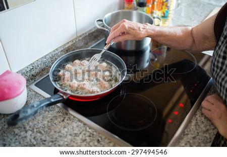 Elderly woman frying meatballs in the kitchen - stock photo