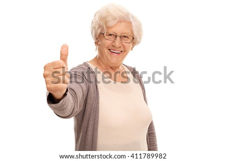 Elderly woman giving a thumb up and looking at the camera isolated on white background - stock photo