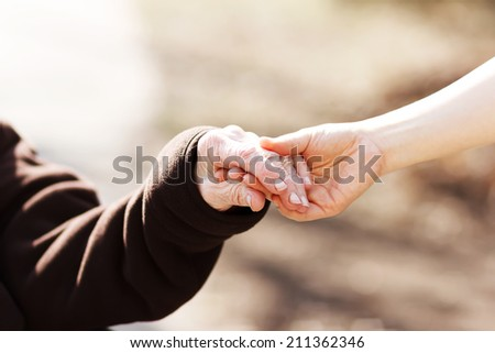 Elderly woman holding hands with young caretaker - stock photo
