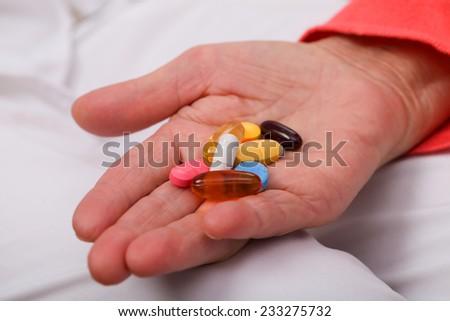 Elderly woman holding pills in her wrinkled hand - stock photo