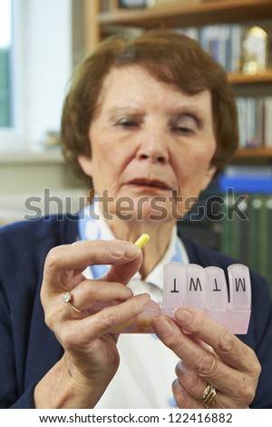 Elderly woman holing medication infront of her - stock photo