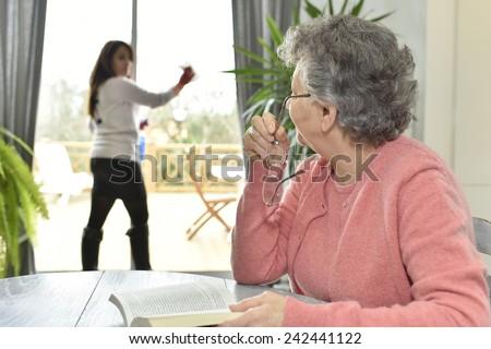 Elderly woman in nursing home reading book  - stock photo