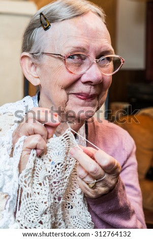 Elderly woman in pink sweater crocheting with demure smile - stock photo