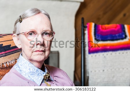 Elderly woman in pink sweater seated in living room - stock photo