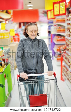 Elderly woman in supermarket - stock photo