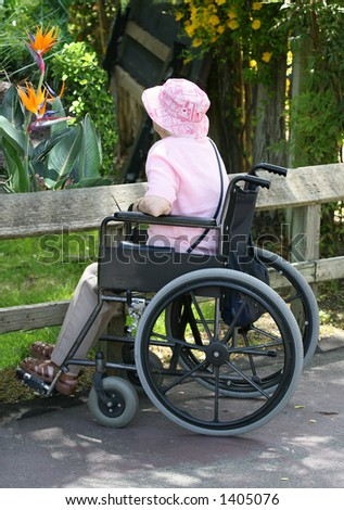 Elderly woman in wheelchair looking at flowers