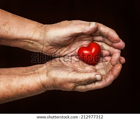 elderly woman keeping red heart in her palms isolated on dark background, symbol of care and love - stock photo