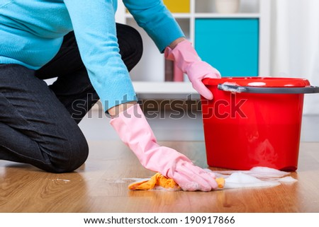 Elderly woman kneeling, doing floor cleaning at home - stock photo