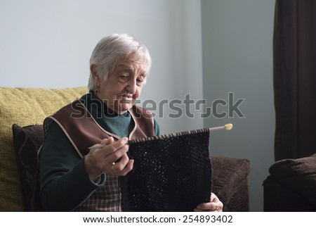 Elderly woman knitting at home. Woman is focus in her activity. - stock photo