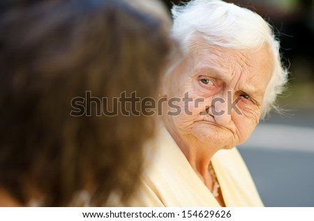 Elderly woman listening to the social worker - stock photo