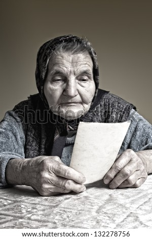 Elderly woman looking at old photos, reminisce about the past. Selective focus on photos. - stock photo