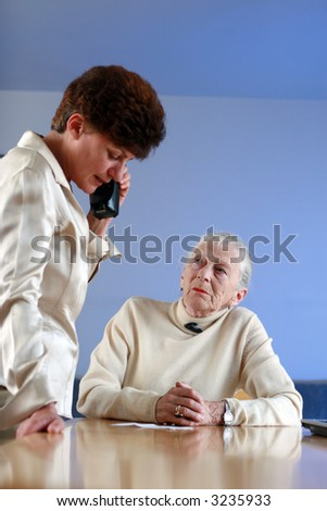 Elderly woman on appointment with social worker. Shallow DOF, focus on elderly lady. - stock photo