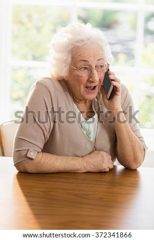 Elderly woman phone calling at home - stock photo