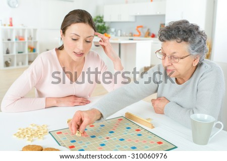 Elderly woman playing a board game - stock photo