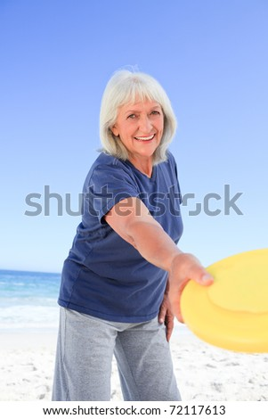 Elderly woman playing freesby - stock photo
