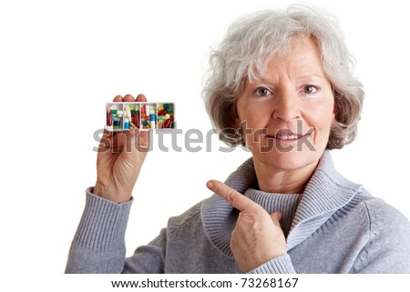 Elderly woman pointing to a pill dispenser with her index finger - stock photo