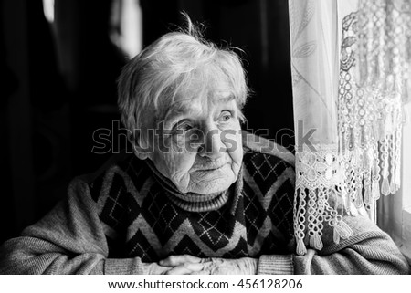 Elderly woman portrait looking out the window. Black-and-white photo of high contrast. - stock photo