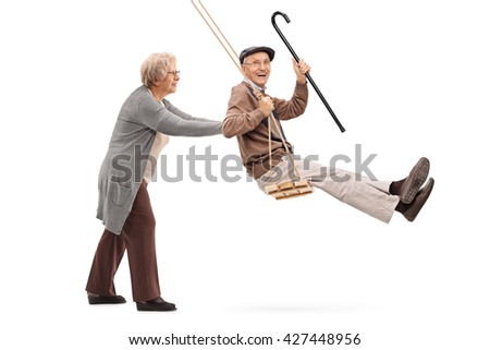 Elderly woman pushing a man on a wooden swing isolated on white background - stock photo