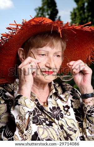 Elderly woman putting on glasses. Lovely straw hat and rich red lipstick - stock photo