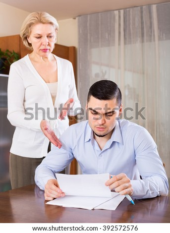 Elderly woman questioning young man about letters from bank
