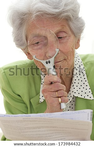 Elderly woman reading documents with magnify glass  - stock photo