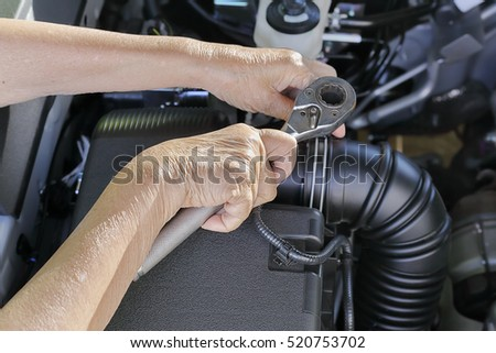 Elderly woman repairing her car