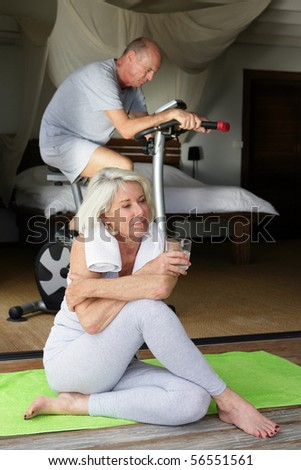 Elderly woman resting with a glass of water near a man doing bike - stock photo