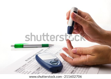 elderly woman's hand with blood drop on finger, near lie glucometer, medicine form and pen on white background with  place for your text - stock photo