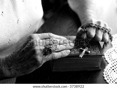 Elderly Woman's Hands Holding Her Bible and Rosary - stock photo