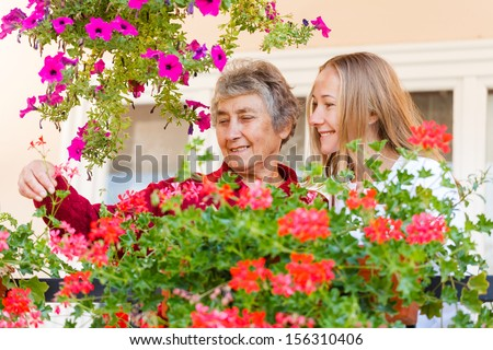 Elderly woman shows her flowers to her assistant - stock photo